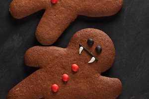 Homemade gingerbread cookies for Halloween in the form of gingerbread men vampire on dark concrete background. Top view