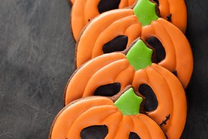 Homemade gingerbread cookies for Halloween in the form of pumpkins on dark concrete background. Top view