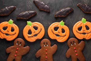Homemade gingerbread cookies for Halloween in the form of pumpkins, gingerbread men and bats on dark concrete background. Top view