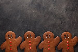 Homemade gingerbread cookies for Halloween in the form of gingerbread men vampire on dark concrete background with copy space. Top view