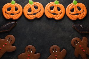 Halloween pumpkin, gingerbread man and bats cookies overhead shot with copy space. On dark concrete background
