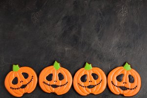 Homemade gingerbread cookies for Halloween in the form of pumpkins on dark concrete background with copy space. Top view