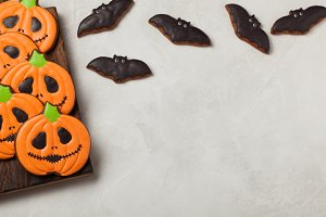 Homemade ginger cookies in the shape of pumpkins and bats on Halloween. On the lighter concrete background. Top view with copy space