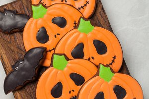 Homemade ginger cookies in the shape of pumpkins and bats on Halloween. On the lighter concrete background. Top view