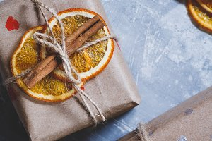 View of christmas gift boxes in a kraft paper decorated dried orange slices, cinnamon sticks and a leaf of a tree.