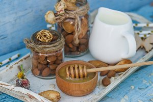 Honey in the wooden bowl, almonds and jar with milk on the wooden tray