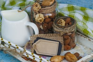 Almonds in the glass, jar with milk on the wooden tray and decorative tag
