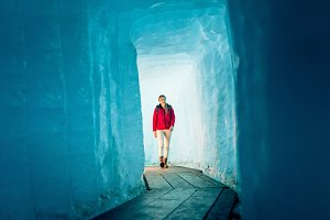Young Woman Hiking Through Glacier Cave