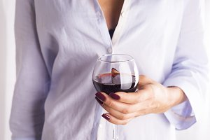 girl in a shirt with a glass of red wine