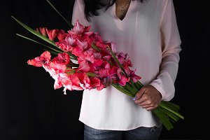 woman holding bouquet from pink gladiolus
