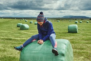 woman on a hay bales in a field
