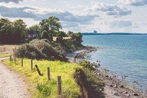 Baltic coastline. Escarpment slope lead to pebble beach. People walking along the shore hanseatic City of Luebeck - Travemuende, Germany