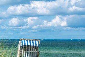 Rainy clouds above beach with blue colored roofed chairs in Travemunde. Germany