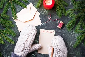Girl in mittens writing letter for Santa