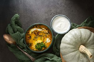 Autumn meal. Soup of ripe pumpkin, sour cream, herbs. Holiday Hallow. Dark background.