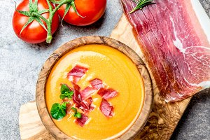 Spanish tomato soup Salmorejo served in olive wooden bowl with ham jamon serrano on stone background. Top view