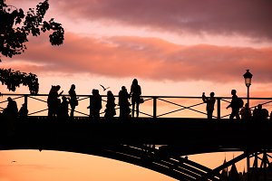 Paris. People on bridge at sunset