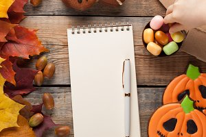Blank white Notepad with pen on background of autumn leaves and candy on Halloween gummy candy, pumpkins and gingerbread cookies on old wooden background. A small child takes candy