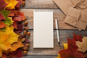 Blank white Notepad with pen and autumn leaves on old wooden background. Greeting card for Halloween. Top view