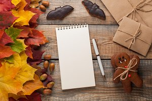 Blank white Notepad with pen on background of autumn leaves and candy on Halloween in the form of pumpkins and bats on the old wooden background. Greeting card for Halloween.