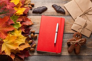 Red notebook and cookies for Halloween in the form of bats and gingerbread men-vampires on the old wooden table. Mixed maple autumn leaves and acorns next to a closed notebook