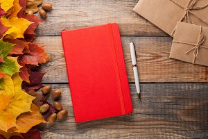 Red notebook with pen and paper envelopes on old wooden table. Mixed maple autumn leaves and acorns next to a closed notebook