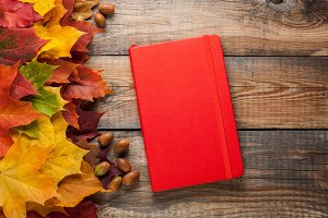 Red Notepad on old wooden table. Mixed maple autumn leaves and acorns next to a closed notebook