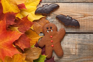 Homemade biscuits in the form of gingerbread men vampire for Halloween. Autumn maple leaves on old wooden background. Top view