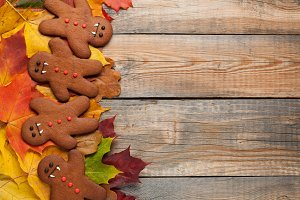 Homemade biscuits in the form of gingerbread men vampire for Halloween. Autumn maple leaves on old wooden background. Top view with copy space