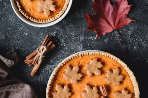 Thanksgiving or Halloween Pumpkin Pies on dark background