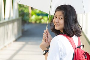 Young woman holding a white umbrella