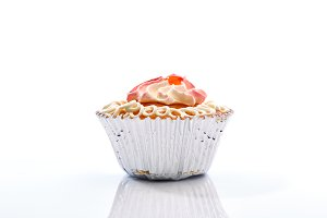 An isolated cupcake with sprinkles on a white background