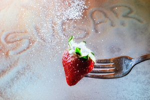 Strawberry on a fork and sugar