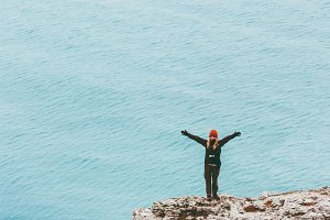 Happy traveler on cliff above sea