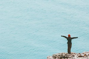 traveler standing on cliff above sea