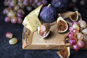 Ripe grapes and figs on dark wooden table