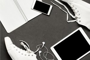 Stylish casual Flat lay Of White Sneakers On black Background with phone, headphones, tablet, copy book
