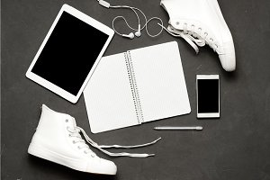 Flat lay Of White Sneakers On black Background with phone, headphones, tablet, copy book