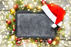 Classic christmas and new year composition chalk board, balls, toys, candy, fir branches on vintage wooden background
