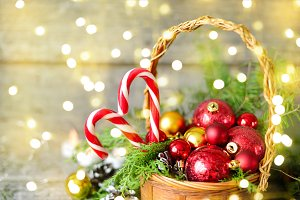 Christmas Basket with Gifts and Shining lights. Red balls, Pine cones, lollipop on Wooden Table