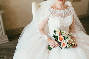 Gorgeous bouquet of white and orange flowers in the hands of the charming woman in a white dress. Bride sit on the chair near the window
