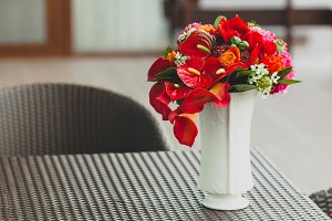 A bouquet of different red flowers in a vase on a table. Close-up. Artwork