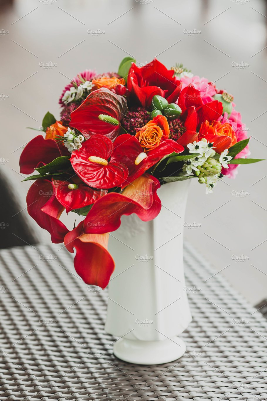 A Bouquet Of Different Red Flowers In A Vase On A Table Close Up