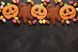 Halloween pumpkin, bat and gingerbread man-vampire cookies and colorful candy overhead shot with copy space