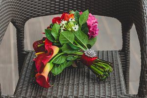 Wedding bouquet with bright red flowers and ribbon with a silver brooch on the stalk. Close-up. Artwork