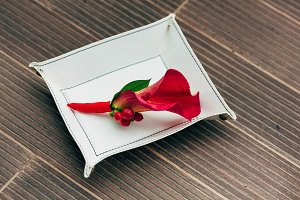 Wedding boutonniere from red calla on the white pedestal. Close-up. Artwork