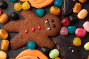 Halloween pumpkin, bat and gingerbread man-vampire cookies and colorful candy overhead shot