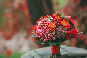 Rustic wedding bouquet with red, orange and bordeaux roses, berries, and other greens on aged wooden logs. Artwork. Close-up.