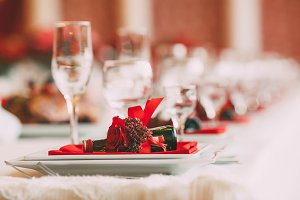 Festive wedding table setting. Dishes decorated with a red flower and accessories for celebration. Artwork