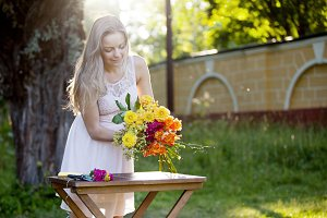 Young beautiful woman florist. The girl in the Park draws a bouquet. Outdoor